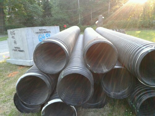 High Density Polyethylene (HDPE) corrugated plastic drainage pipes can be found here in our yard.