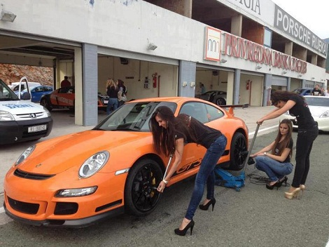 Flat bottomed girls in heels attempt to change tires on an orange Porsche 911 GT3